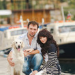 Young couple playing with a dog in the harbor — Stock Photo #48915983