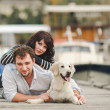 Young couple playing with a dog in the harbor — Stock Photo