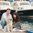 Young couple playing with a dog in the harbor — Stock Photo #48916401