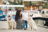 Mother and son with a golden retriever, sitting on the quay — Stock Photo
