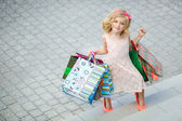 Fun preschool girl walking with bags. — Stock Photo