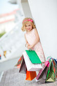 Little girl fashion with packages at the Mall. — Stock Photo