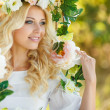 Beautiful woman with a wreath of flowers. — Stock Photo #49553333