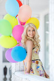 A young woman with large colourful latex balloons — Stockfoto