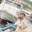 Father and son sits with dogs on a bench near the sea — Stock Photo #49639427