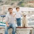 Father and son sits with dogs on a bench near the sea — Stock Photo #49639545