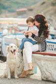 Madre e hijo en el paseo marítimo con un perro — Foto de Stock