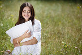 The girl with a pillow on the fresh spring grass. — Stock Photo