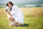 Beautiful woman plays with the dog on the Meadow — Stock Photo