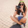 A girl takes pictures the old camera on city streets. — Stock Photo #49793317