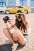 A girl takes pictures the old camera on city streets. — Stock Photo