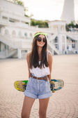 Beautiful and fashionable young woman posing with skateboard — Stock Photo