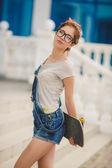 Jonge vrouw met een skateboard op de straat van de stad — Stockfoto