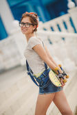 Young woman with a skateboard on the street of the city — Stock Photo