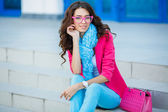 Stylish beautiful girl sitting on stairs in colorful clothes — Stockfoto