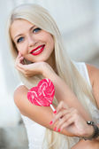 Elegant blonde with a lollipop in the shape of a heart — Stock Photo