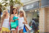 Tre flickor med shopping väskor och shoppa. — Stockfoto