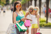 Three girls with shopping bags and go shopping. — Stock Photo