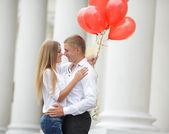 A young couple in love with red balloons on the street — Stock Photo