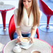 Pretty young woman sitting in the cafe with a cup of tea — Stock Photo #9237715
