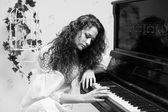 Monochrome shot of romantic girl playing piano — Stock Photo