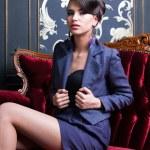 Elegant girl sitting on red luxury sofa — Stock Photo