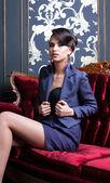 Elegant girl sitting on red luxury sofa — Photo