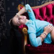Girl laying on red sofa — Stock Photo