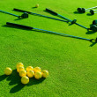 Iron golf club and golf ball on green grass — Stock Photo #27710115