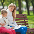 Mom and daughter on a park bench — Stock Photo