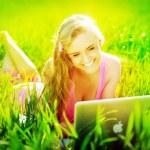 Yeşil çimenlerin üzerinde otururken dizüstü olan kadın — Stok fotoğraf