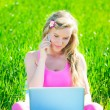 Young woman with laptop sitting on green grass — Stock Photo #41199997