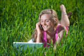 Young woman with laptop sitting on green grass — Stockfoto