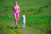 Young attractive sport girl running with dog in park — Stock Photo