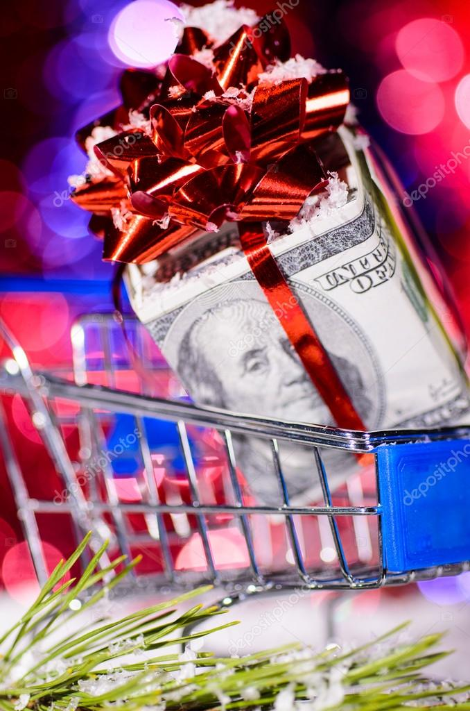 Shopping cart with money against blurred lights on christmas tree — Stock Photo #14888993