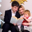 Couple with baby are reading — Stock Photo