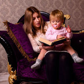 Mother and her baby are reading — Stock Photo