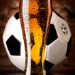 Glass of lager with soccer ball — Stock Photo
