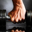 Male hand is holding metal barbell — Stock Photo