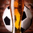 Stock Photo: Glass of lager on table with soccer ball