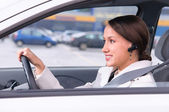 Talking phone in a car using a headset — Stock Photo