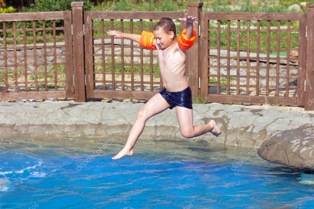 Child jumps into the pool with water  Stock Photo #12015439