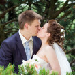 Happy bride and groom kissing in nature — Stock Photo
