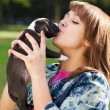 Girl kissing her puppy — Stock Photo