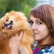 Stock Photo: Young womholding pomeranian