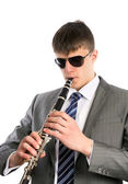 Young musician plays the clarinet in sunglasses — Stock Photo