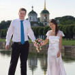 Bride and groom near a pond on the background of the church — Stock Photo
