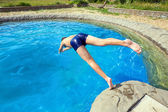 Teenager jumping into pool — Stock Photo