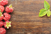 Raspberry on old wooden plank — Stock Photo