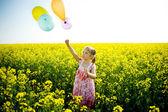 Balões em um campo amarelo — Fotografia Stock
